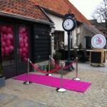 Roze kunstgras loper met afzetpalen en roze koorden en roze heliumballonnen
